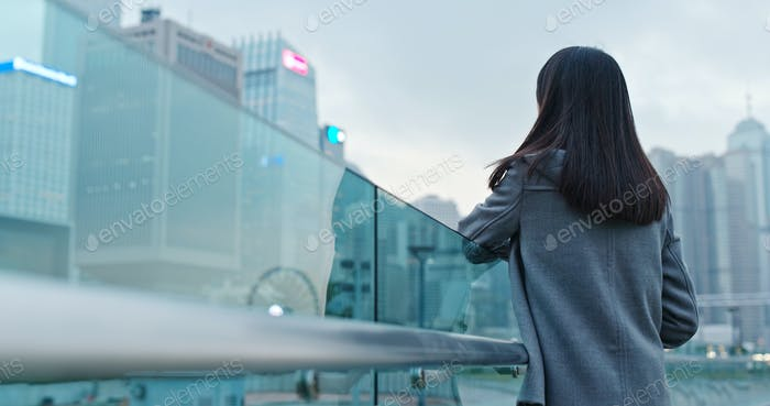 Woman look at far away in the city