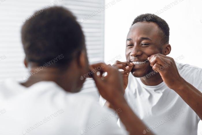 Toothy Afrikaner Zahnseide Zahnseide mit Zahnseide stehend im Badezimmer
