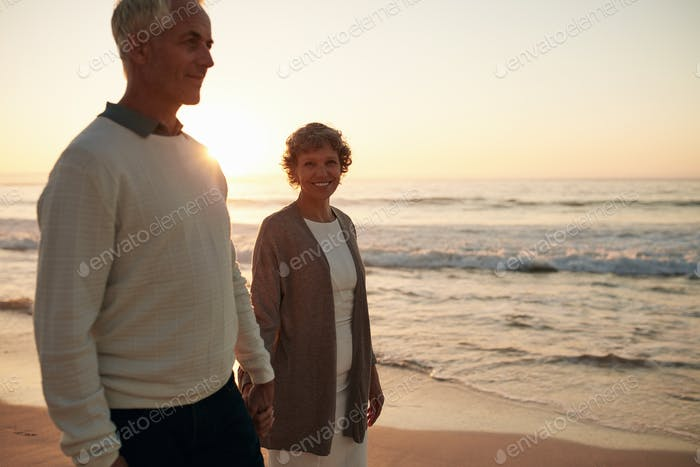 Senior woman with her husband strolling on the beach