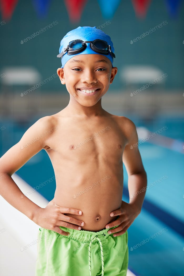 Portrait Of Boy Standing By Edge Of Swimming Pool Ready For Lesson