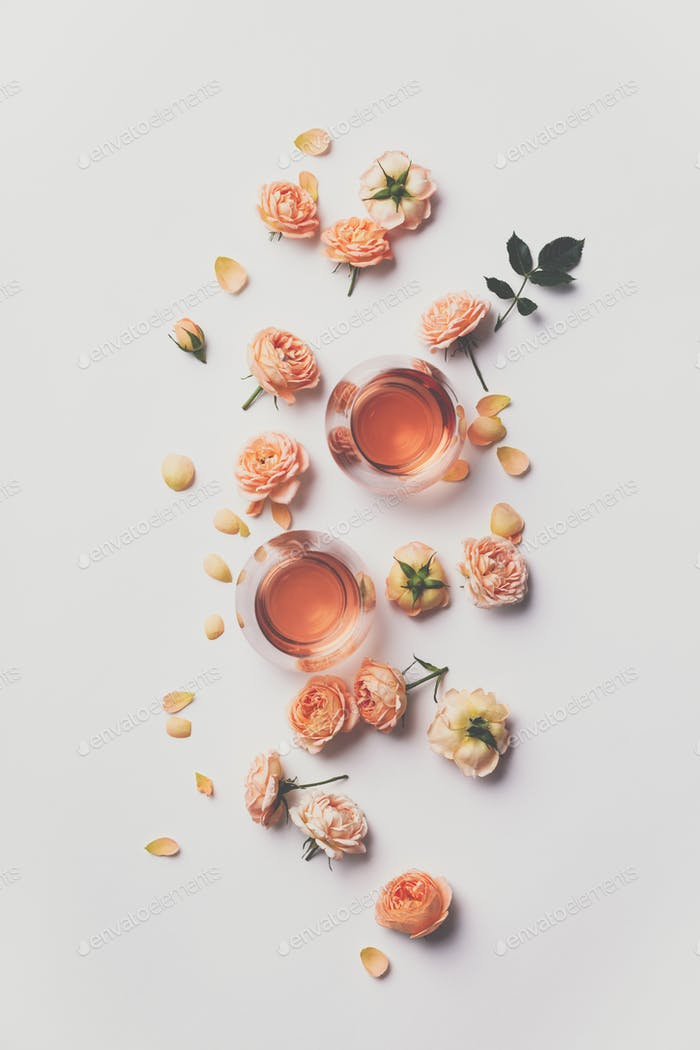 Rose wine and roses on white background