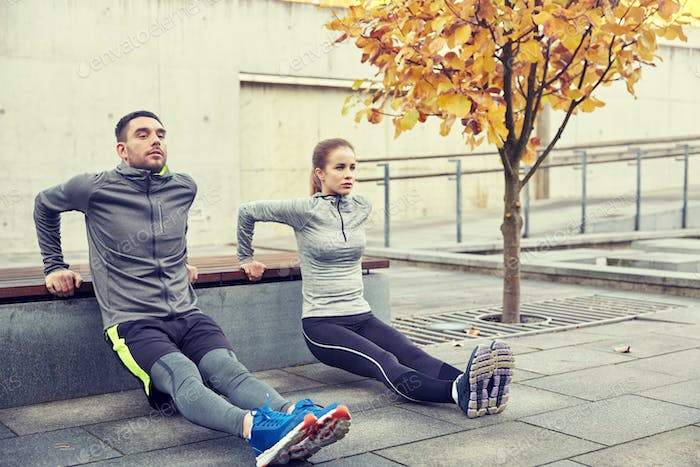 couple doing triceps dip on city street bench