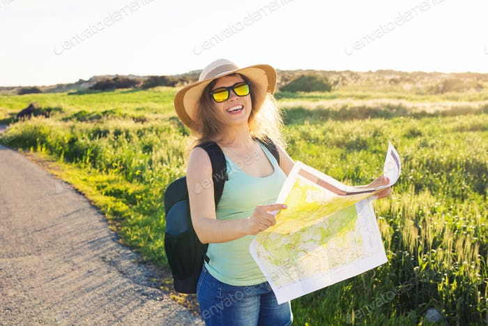 woman traveler with backpack checks map to find directions