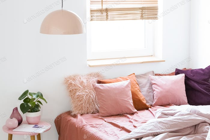 Pink pillows on bed next to table with plant in bright bedroom i