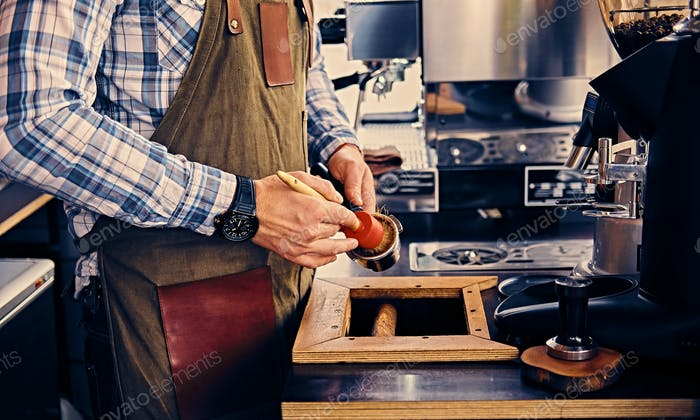 Close up image of a man cleans coffee machine with a tassel.