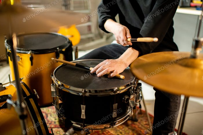 Hand of young musician putting drumstick on black drum during rehearsal