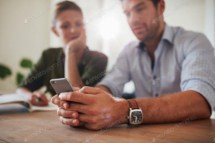 Paar zusammen am Tisch sitzen mit Smartphone