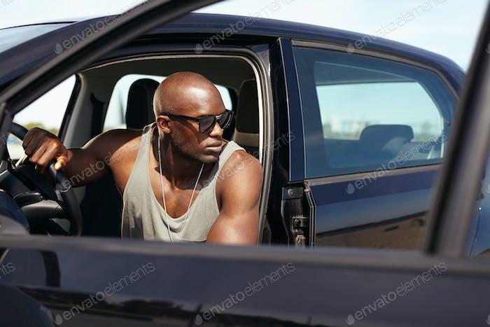 Muscular man on road trip.