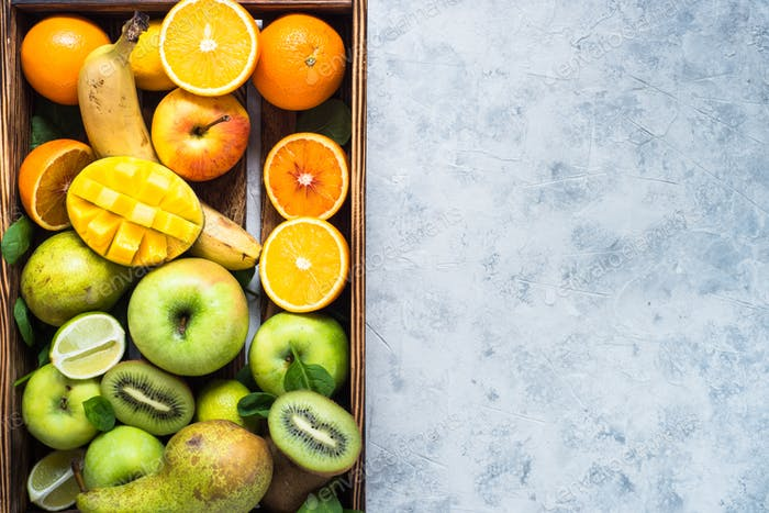 Green yellow and orange fruits in wooden tray.