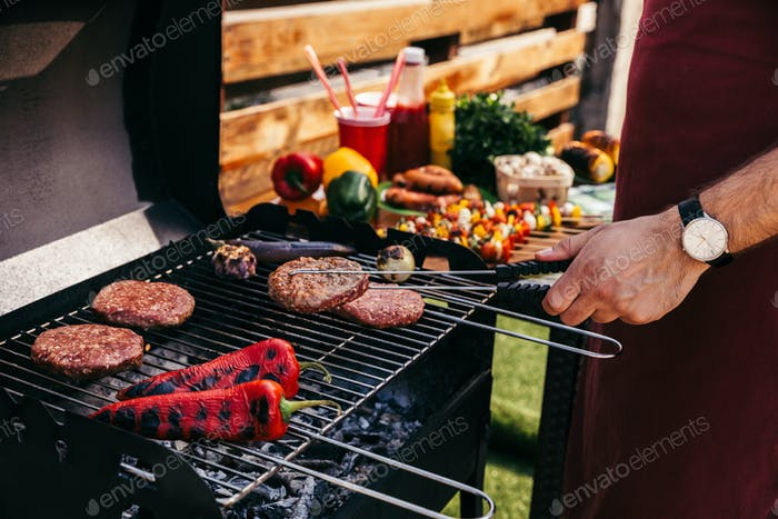 Chef Cooking Patties And Vegetables Grilled For Outdoors Barbecue