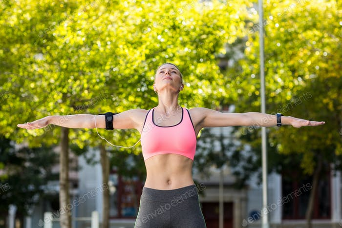 A beautiful athlete stretching her arms on a sunny day