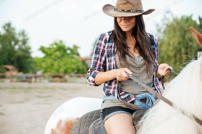 Beautiful young woman cowgirl sitting and riding horse in village