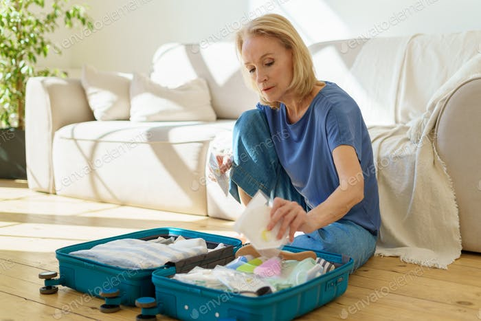 Elderly female packing holding respirator while packing suitcase for travel trip during covod19