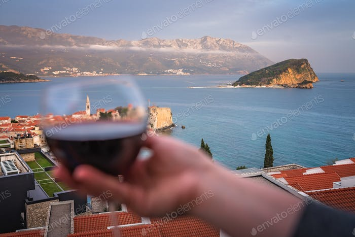 Woman holding glass with red wine