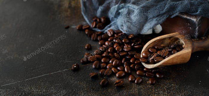 Coffee beans and a wooden spoon  on a dark background