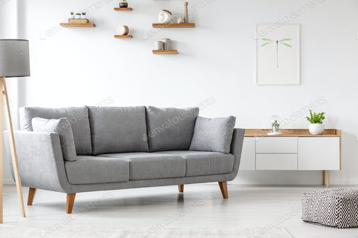 Simple, gray sofa standing next to a white cupboard in living ro
