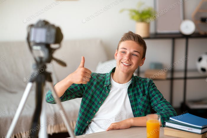Cheerful teenager showing thumb up, broadcasting from home