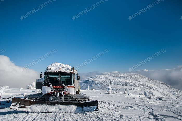 Red ratrak snowcat in winter mountains