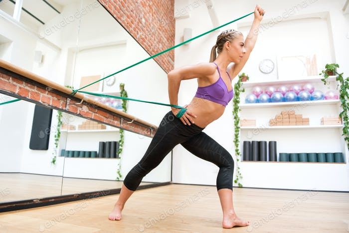Young woman exercising with flex band at gym