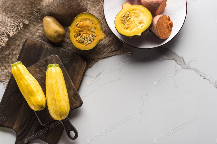 Wooden Cutting Boards With Zucchini, Potato, Pumpkin And Plate With Yam on Marble Surface