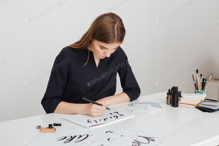 Portrait of young beautiful lady sitting at the white desk and writing alphabet on paper isolated