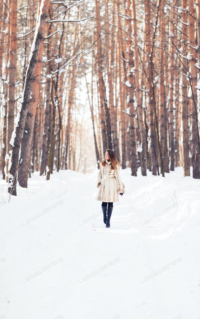 Girl walking in snow. Winter, cold and people concept