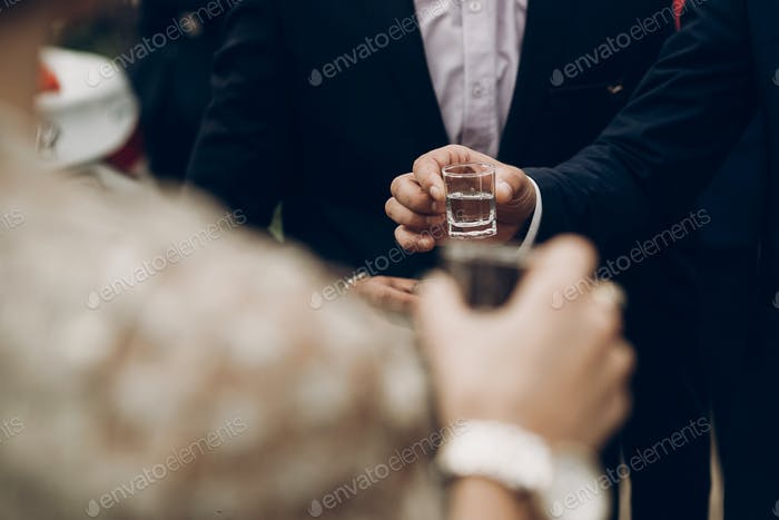 people holding glasses of vodka and toasting at wedding reception