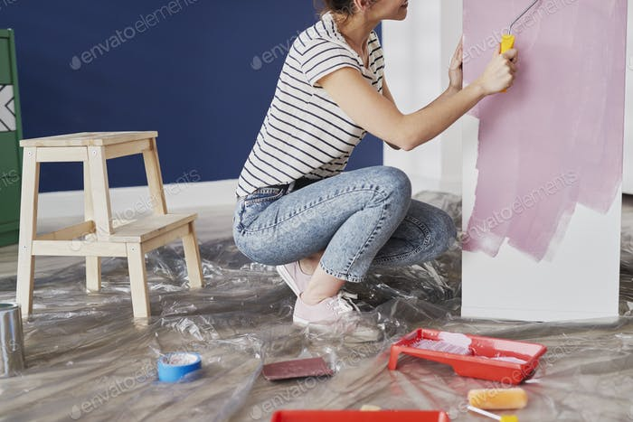Young woman repainting furniture with DIY