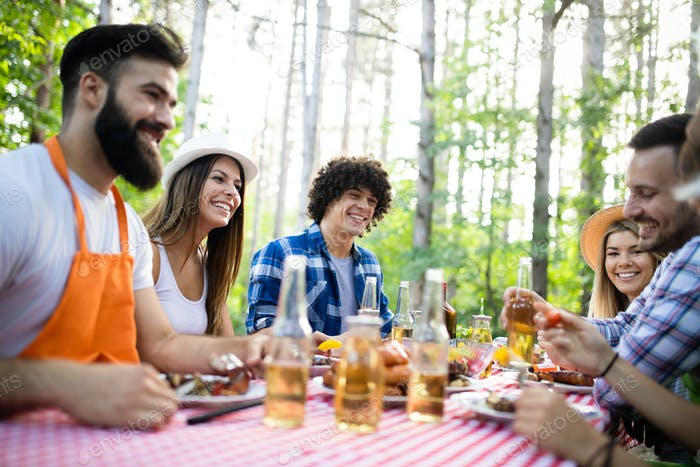 Happy friends camping and having a barbecue in nature