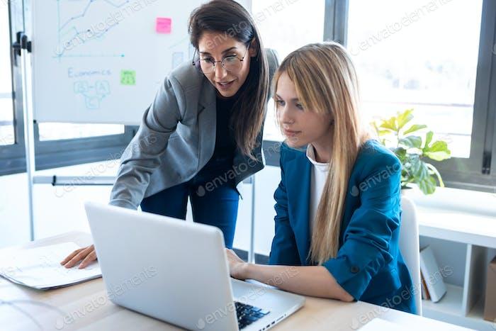 Zwei Geschäftsfrauen arbeiten zusammen mit Laptop im Büro.