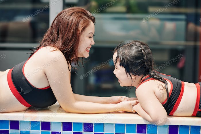 Joyful mother after daughter after swimming