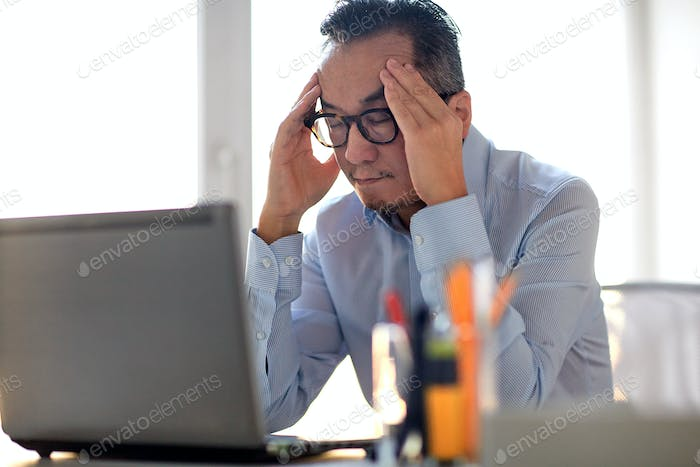 businessman in eyeglasses with laptop at office