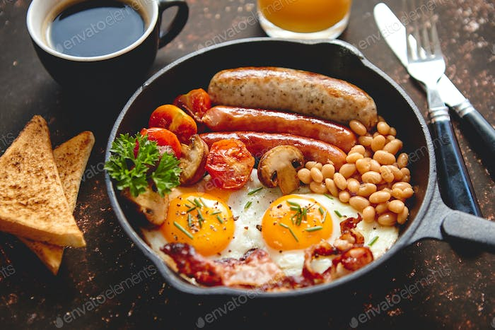 Full English breakfast on dark rusty background