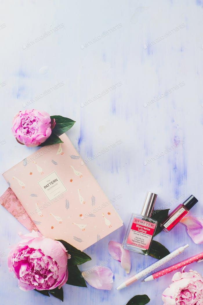 Minimaler flacher Lag mit Pfingstrosenblüten, Blütenblättern, Schreibwaren und Notizbüchern auf weißem Hintergrund