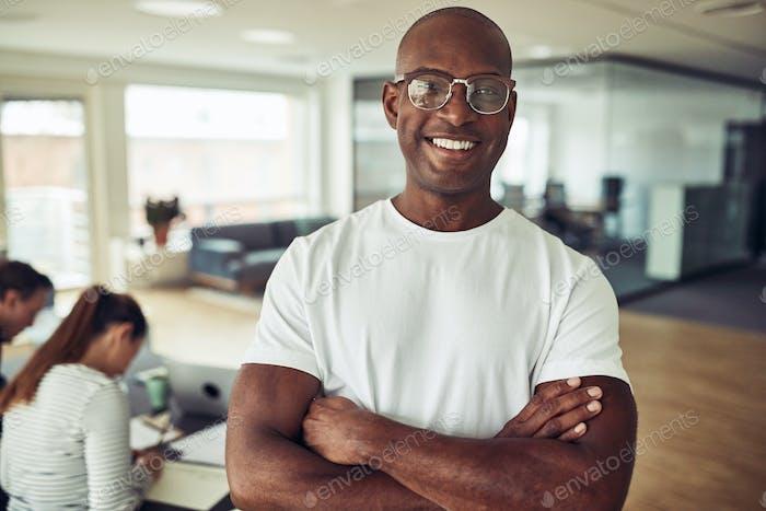 Afrikanischer Geschäftsmann lächelnd mit Kollegen bei der Arbeit im Hintergrund