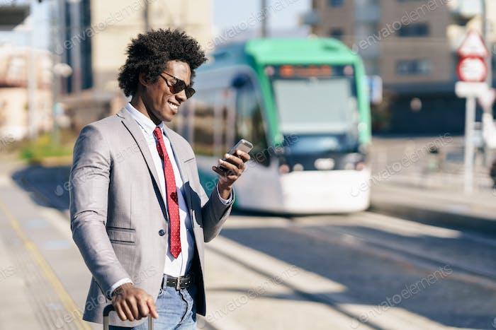 Hombre de negocios negro usando traje esperando su tren