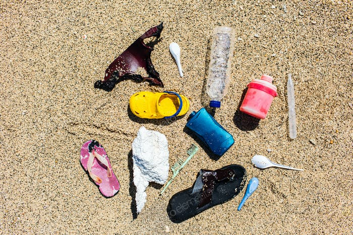 Various types of plastic waste collected on the beach. Single-use spoons, rubber shoes, different