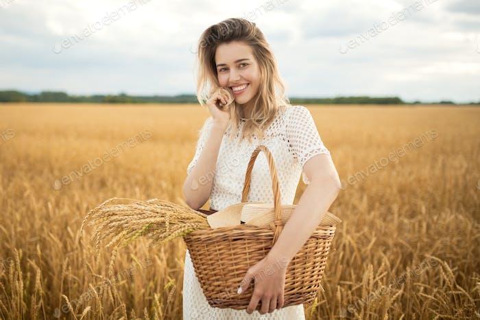 Junge attraktive Frau und goldene Weizenfeld. Erntekonzept