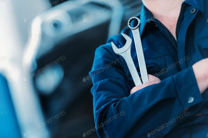 Closeup shot of an automechanic in overalls holding wrench and ring spanner