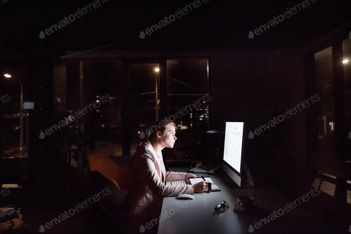 Businesswoman in front of computer screen in office at night.