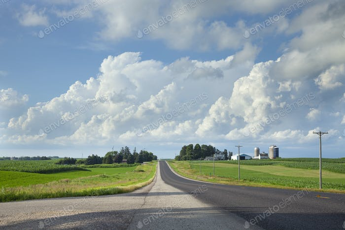 Rural highway in southern Minnesota with fields and a farm beneath dramatic clouds
