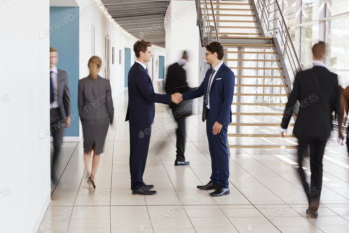 Two white businessmen shaking hands in a busy modern lobby
