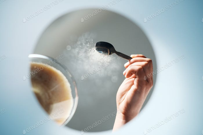 Man Adding Sugar To Coffee For Morning Breakfast