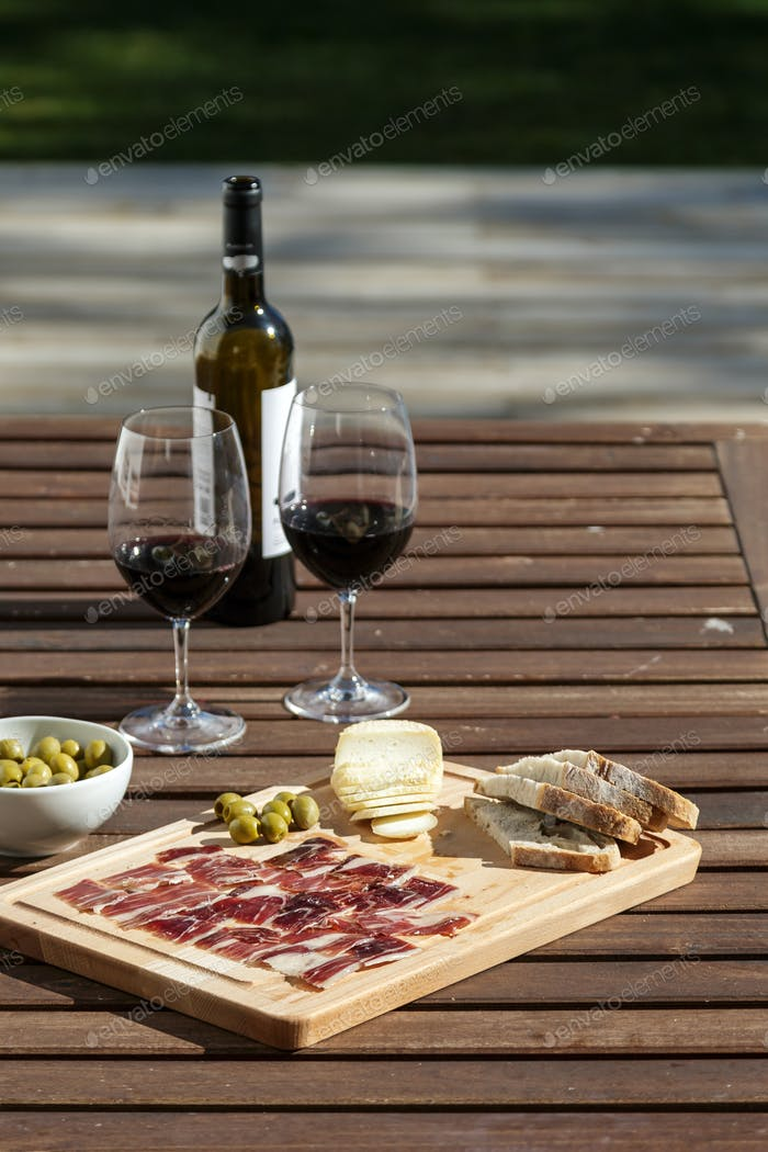 outdoor table setting with red wine cheese and bread
