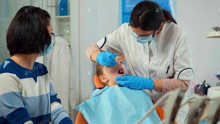 Dentista pediátrico con máscara de tratamiento de los dientes a la niña del paciente