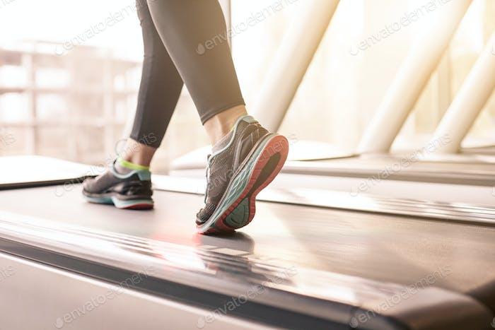 Frau läuft in einem Fitnessstudio auf einem Laufbandkonzept für Sport, Fitness und gesunden Lebensstil