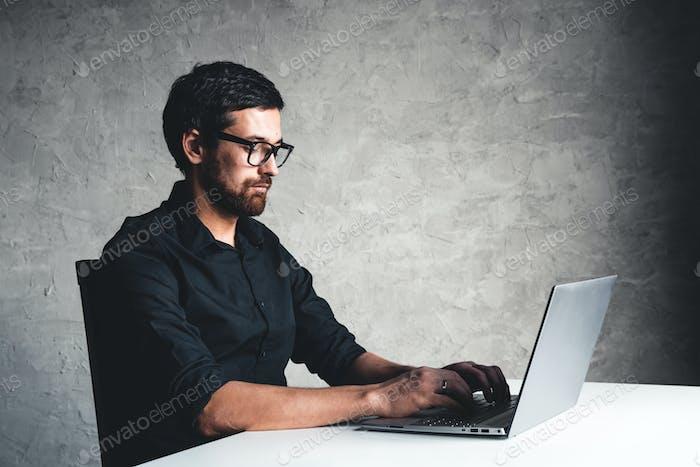 Un hombre se sienta con una computadora portátil en una camisa negra. Concepto de negocio, trabajo. Rutina de oficina. Actividades de propiedad