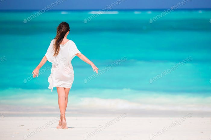 Young beautiful girl on tropical beach at caribbean vacation