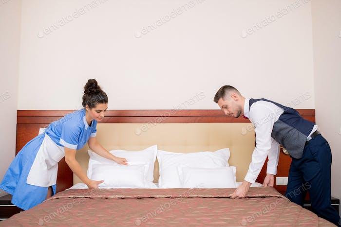Junge Portier und Kammermädchen beugen über Bett, während es in den Morgen