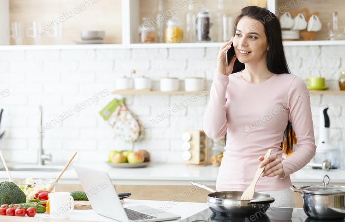 Young woman cooking and talking on cellphone at kitchen